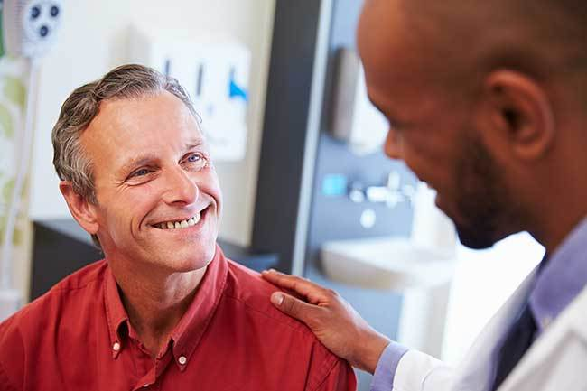 Doctor looking down to smiling man in red